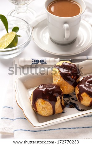 Homemade profiteroles with chocolate cream on the white background