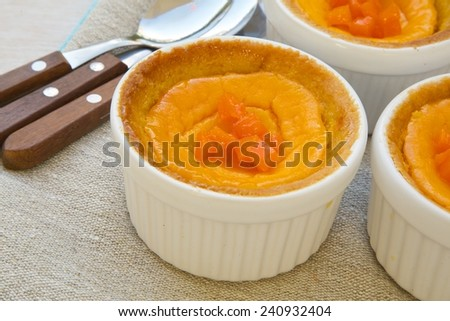 Homemade pumpkin cheese cakes in white ceramic moulds.Dessert spoons on a sackcloth in the background. - stock photo