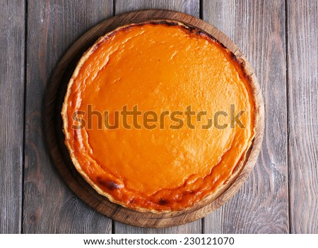 Homemade pumpkin pie on wooden background - stock photo