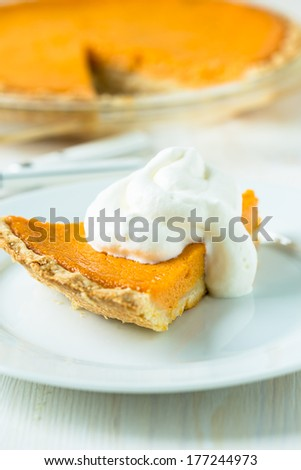 Homemade pumpkin pie with whipped cream on white plate
