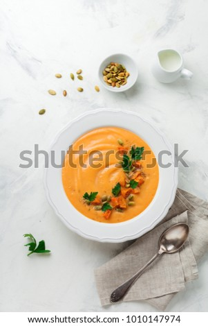 Homemade pumpkin soup in white ceramic dish on an old concrete or stone background. Selective focus.  Top view. Copy space.