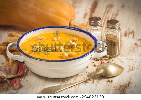 Homemade pumpkin soup on rustic wood table - stock photo