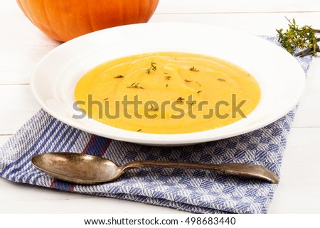 homemade pumpkin soup with fresh thyme in a deep plate on a kitchen towel