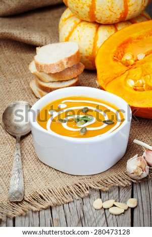 Homemade pumpkin soup with garlic and fresh cream on rustic wooden table, selective focus - stock photo