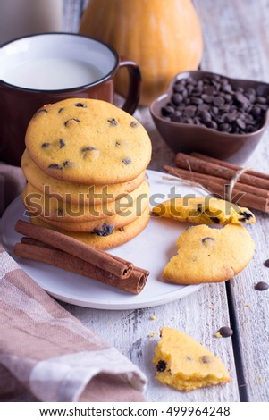 Homemade Pumpkin Spice Cookies with chocolate chips or drops with brown cup of milk on Halloween,cinnamon sticks. Copy space