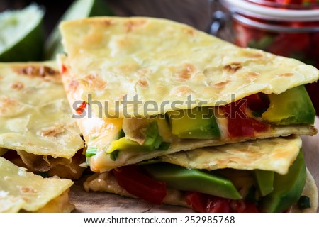 Homemade quesadilla,  corn tortilla filled with cheese,  avocado, chopped onion, and  chiles - stock photo