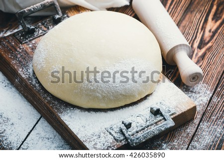 Homemade raising yeast bread dough and rolling pin on rustic wooden table