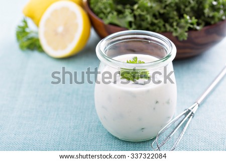 Homemade ranch dressing in a small jar with herbs - stock photo