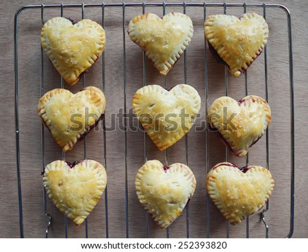 Homemade Raspberries, lemon Pies crust hearts on a cooling rack  - stock photo