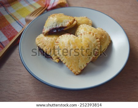 Homemade Raspberries, lemon Pies crust hearts with sugar on top on the plate - stock photo