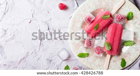 Homemade raspberry popsicles on plate with ice and berries. Summer food concept with copy space for text. Top view. - stock photo