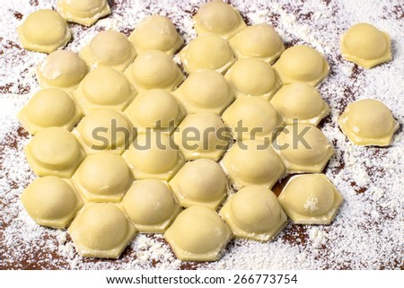 Homemade ravioli with meat prepared for cooking on the table, sprinkle with flour. Selective focus - stock photo
