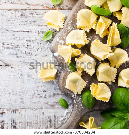 Homemade raw Italian saccottini filled with green pesto on wooden vintage cutting board with basil leaves. Selective focus. Top view. - stock photo