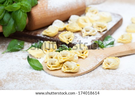 Homemade raw Italian tortellini and basil leaves on a table - stock photo
