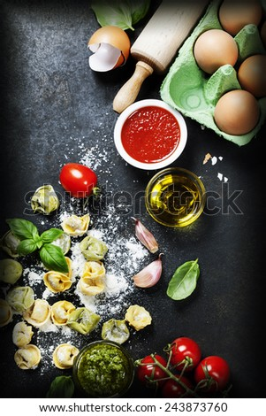 Homemade raw Italian tortellini, basil leaves  with flour and  tomatoes on dark vintage background - stock photo