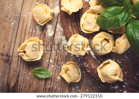 Homemade raw Italian tortellini on wooden vintage cutting board with a rolling pin. Selective focus. Retro style toned.  - stock photo