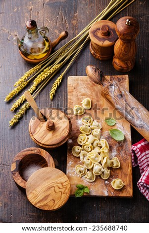 Homemade raw Tortellini and basil leaves on dark wooden background - stock photo