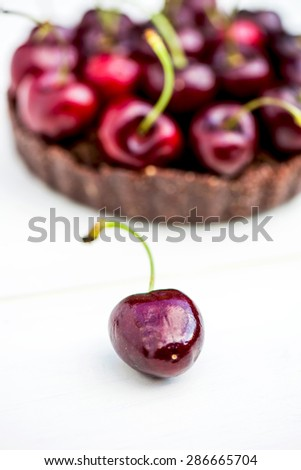 Homemade Raw Vegan Cherry Tart with Cherry on the foreground, macro shot, selective focus, shallow DOF - stock photo