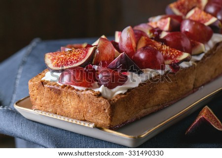 Homemade rectangular Tart with red Grapes, Figs and Whipped cream in white ceramic plate over old wooden table with blue textile rag. Dark rustic style. - stock photo
