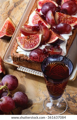 Homemade rectangular Tart with red Grapes, Figs and Whipped cream in white ceramic plate over stone surface in bright sunlight. With vintage glass of red wine - stock photo