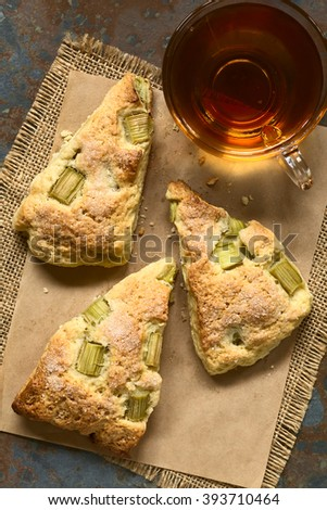 Homemade rhubarb scones with a cup of tea photographed overhead with natural light