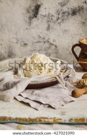 Homemade ricotta, cottage cheese on cheesecloth. Rustic styling - stock photo