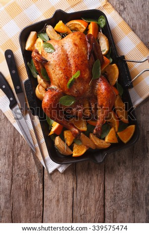 Homemade roasted chicken with apples and oranges in a pan. vertical top view - stock photo