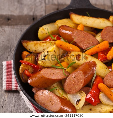 Homemade roasted polish sausages and vegetables dinner. Selective focus. - stock photo