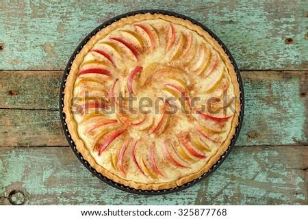Homemade round apple tart on vintage wooden table - stock photo