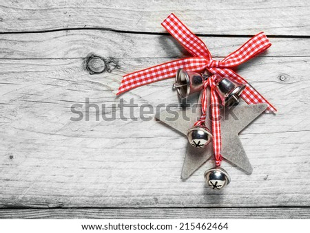 Homemade rustic Christmas decoration with a fresh red and white checked bow holding a star and bells on a weathered cracked wooden background with copyspace - stock photo