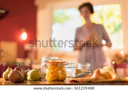 Homemade rustic jar of cut fruits with pears, spatula and table cloth on wooden table. A woman is standing in the blur background of the red kitchen. Vintage old fashioned shot with flare - stock photo