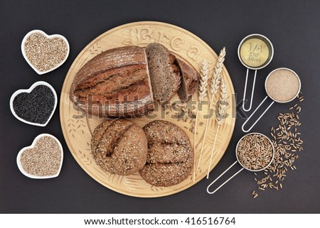 Homemade rye bread loaf and seeded rolls on a wooden board  with oatmeal, poppy and sesame seed in heart shaped bowls and olive oil, yeast and rye grain in measuring scoops. - stock photo