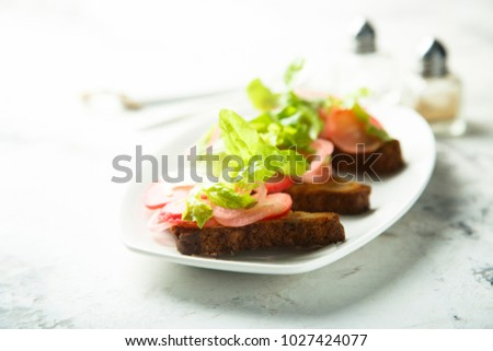 Homemade rye bread toasts with green salad and pickled radish