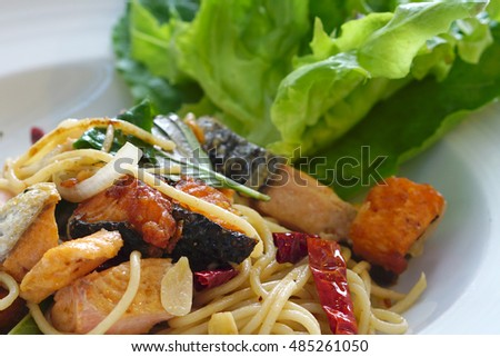 Homemade Salmon and onion with garlic and dried cayenne pepper spaghetti serving with fresh salad