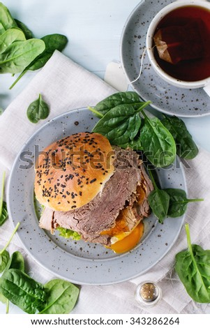 Homemade sandwich with baked meat and soft-boiled egg, spinach salad, salt and cup of hot pocket tea over blue wooden table with white textile. Top view - stock photo