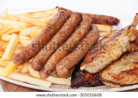 Homemade sausages and grilled meat served with french fries. - stock photo
