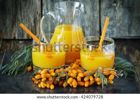 Homemade sea buckthorn soft drink in a glass and ripe sea buckthorn berries on the table. Healthy and diet food. Selective focus - stock photo
