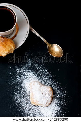 Homemade shortbread cookies, sprinkle with powdered sugar and a cup of coffee, spilling powdered sugar on a black background