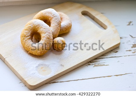 Homemade simple donuts with powdered sugar on the old white light wood  background