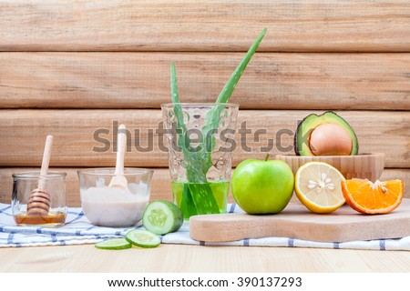 Homemade skin care and body scrub with natural ingredients avocado ,aloe vera ,lemon,cucumber ,orange ,apple, lime and honey set up on on  wooden background.