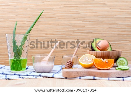 Homemade skin care and body scrub with natural ingredients avocado ,aloe vera ,lemon,cucumber ,orange and honey set up on on  wooden background.