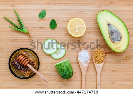 Homemade skin care and body scrub with natural ingredients avocado ,aloe vera ,lemon,cucumber and honey set up on wooden background.