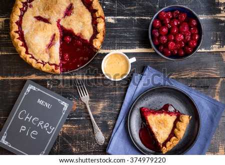 Homemade sliced cherry pie with flaky crust, cup of coffee, bowl with cherries and menu chalkboard on the black wooden table. Top view - stock photo