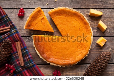 Homemade sliced pumpkin tart pie recipe with cinnamon and nuts on vintage wooden table background. Halloween party traditional dessert. Rustic style - stock photo