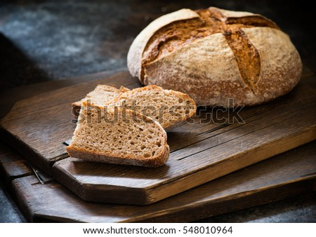 Homemade sliced rye artisan sourdough bread over dark background, selective focus, closeup