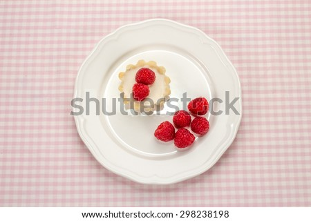 Homemade small cake with cream cheese and fresh garden raspberries in white porcelain plate on a checkered napkin, top view