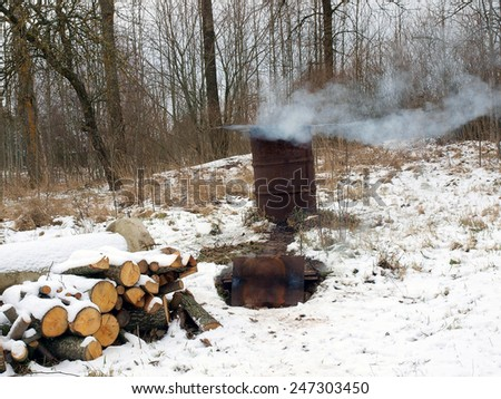 Homemade smoke box from metal barrel smoking meat or fishes      - stock photo