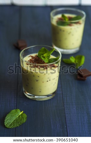 Homemade smoothie with kiwi, banana and chocolate chips, mint leaves and pieces of chocolate on blue rustic background. Conception of healthy food.