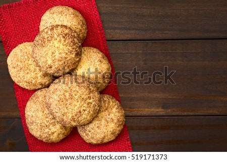 Homemade snickerdoodle cookies with cinnamon and sugar coating, photographed overhead on dark wood with natural light (Selective Focus, Focus on the cookies on the top)