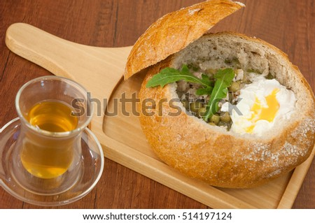 homemade soup with peas and eggs in a bowl of bread on a board and a cup of green tea